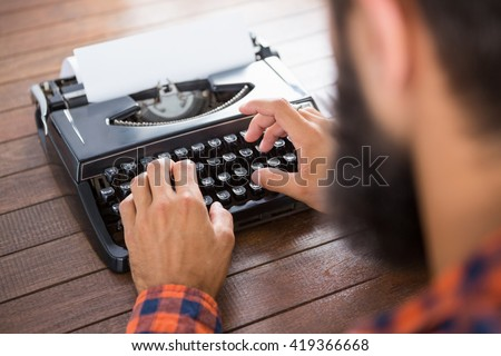 A man is typing on a type writer on his desk - stock photo