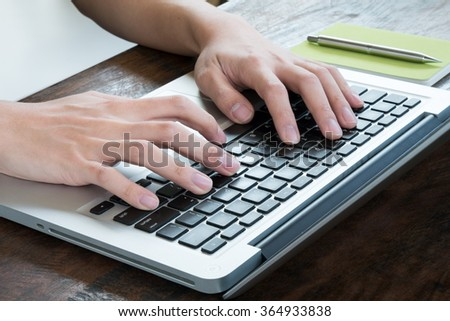 A man is typing on laptop's keyboard, side view.