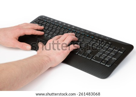 A man is typing with both hands on a black Keyboard. - stock photo