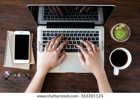 A man is working by using a laptop computer on vintage wooden table. Hands typing on a keyboard. Top view. - stock photo