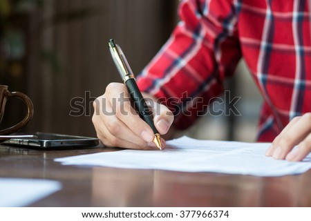 A man is writing/signing on a paper. Focused on a hand with pen. - stock photo