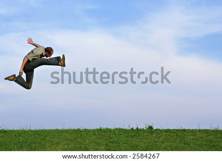 A man jumping very high over a grassy hill against a blue sky - stock photo