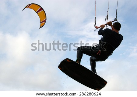 A man kite surfing into a blue sky with clouds