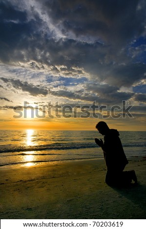 A man kneeling and praying on the beach with dramatic clouds and a golden sunset. - stock photo