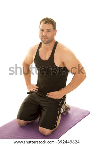 A man kneeling down on his fitness mat, with her hand on her hips. - stock photo