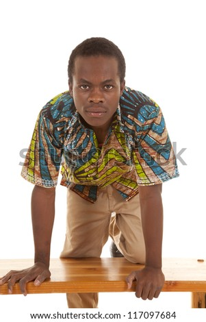 A man kneeling on a bench looking into the camera. - stock photo