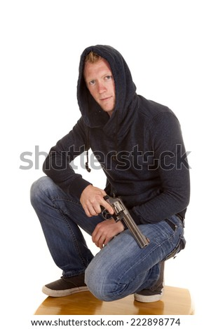 A man kneeling with a pistol across his leg. - stock photo
