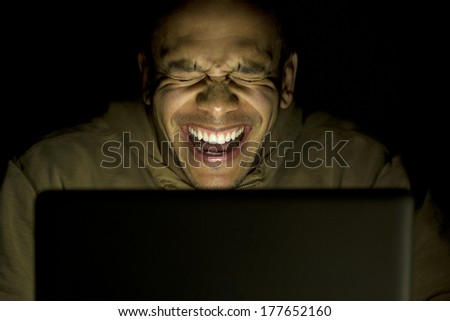 A man laughing whilst using his laptop at night, concept of modern technology use - stock photo