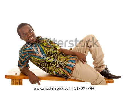 A man laying down on a bench with a big smile on his face. - stock photo