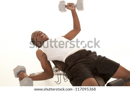 A man laying on a workout bench holding too much weight almost to fall off the bench. - stock photo