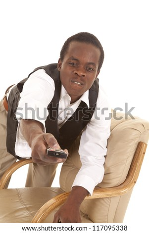 A man leaning over a chair with a remote trying to get it to change a channel - stock photo