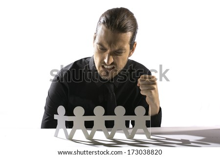 A man leans over a row of cut outs as if to manipulate them with evil intent./Machinations - stock photo