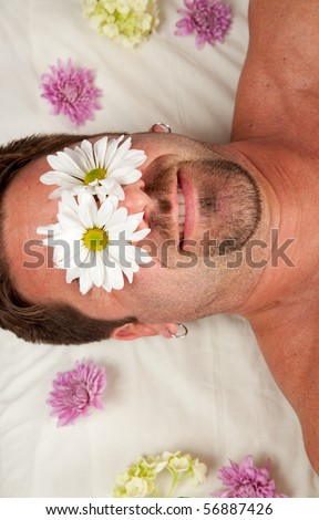 A man lies on a massage table with flowers over his eyes.