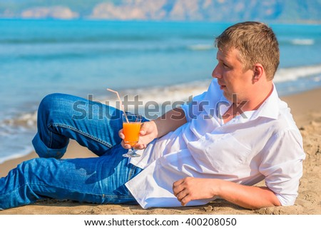 a man lies with a cocktail on the sandy beach in clothes - stock photo