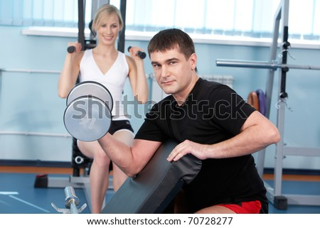 A man lifting a barbell with a woman training on exercise machine in the background - stock photo