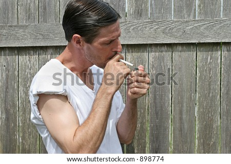 A man lighting up a cigarette.