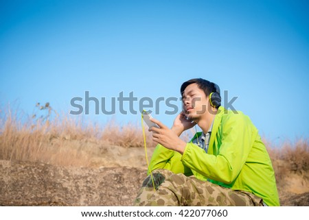 A man listening music headphones from smartphone at natural outdoor