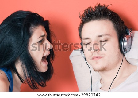 A man listening to music on the headphones while a woman shouting at him - stock photo