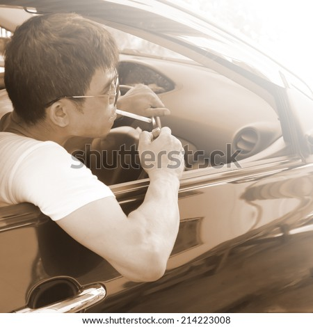 A  man lit a cigarette in a car  - stock photo