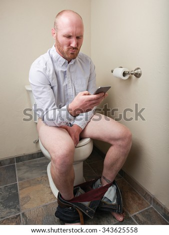 A man looking at his phone while using the toilet - stock photo