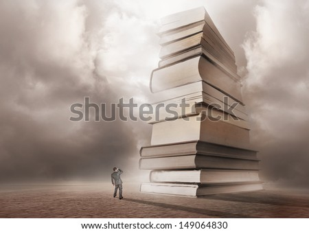 A man looking forwards a mountain of books.