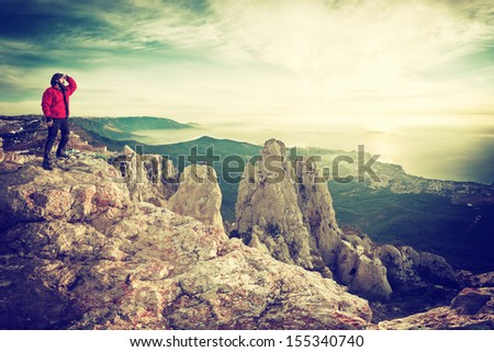 A man looking to the future on top of a mountain, vintage - stock photo