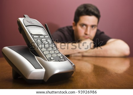 A man looks at a phone as he waits for it to ring - stock photo