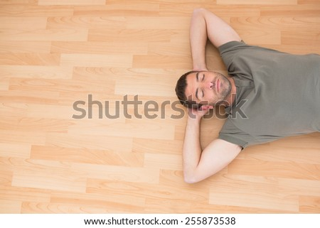 A man lying on floor at home in the living room - stock photo