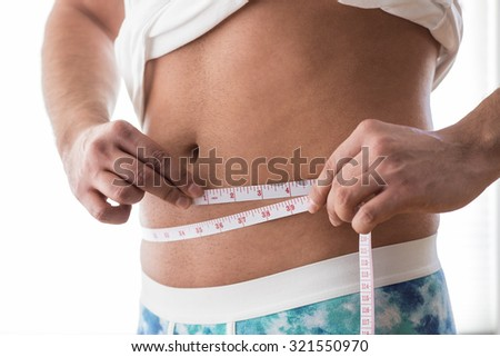 A man measuring his waistline with a tape measure - stock photo