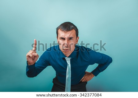 a  man of European appearance thirty years threatens finger on a gray  background - stock photo
