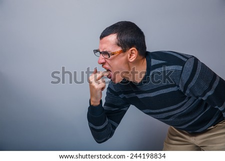 a man of European appearance 30 years sick fingers in the mouth - stock photo