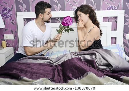 A man offer a rose to her wife in vintage room. - stock photo