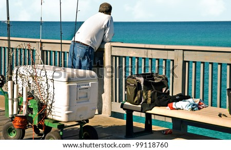 A man on a pier with fishing equipment around him. - stock photo