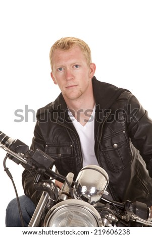 A man on his motorcycle sitting in his black leather jacket looking. - stock photo