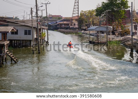 A man on jet ski in Canal waterfront community. - stock photo