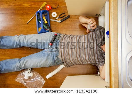 A man on the kitchen floor is fixing the sink. - stock photo
