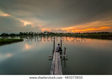 A man on the  pier in the sunset.Image have grain or noise and soft focus.