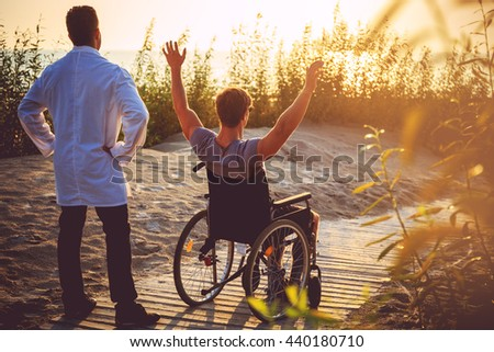A man on wheelchair and his nurse enjoying sunrise on a beach.