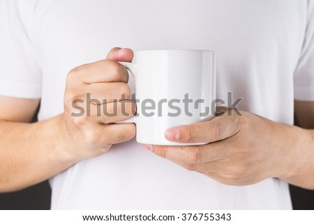 A man on White T-shirt Holding a Coffee mug on Black background