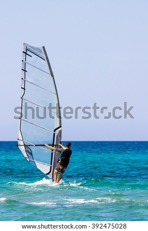 A man on windsurf conquering the waves - stock photo