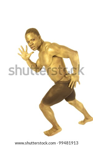 A man painted gold in his running stance.