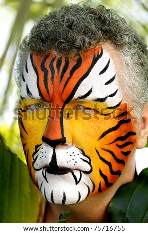 A man painted up like a tiger, looking suspicious. - stock photo