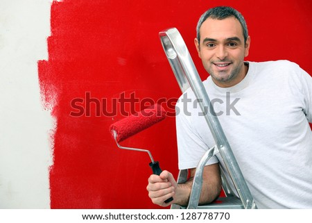 A man painting a wall red - stock photo