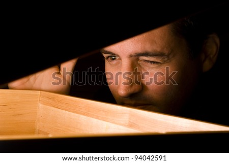 A man peeks into a box - stock photo