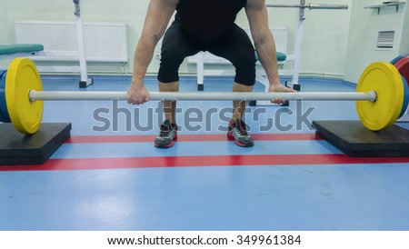 A man performs an exercise with a barbell. Young weightlifter in the gym. Athletic, healthy, muscular guy. Healthy lifestyle concept. Weightlifting.
