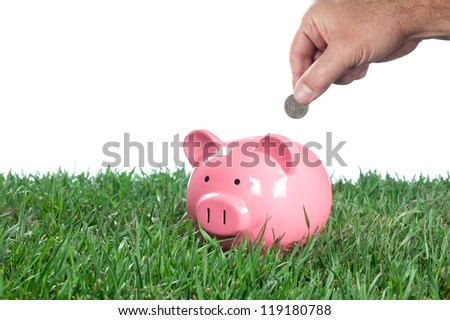 A man places a quarter into his piggy bank to save for the future.