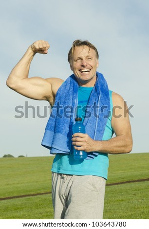 A man playfully flexing his muscles and laughing. - stock photo
