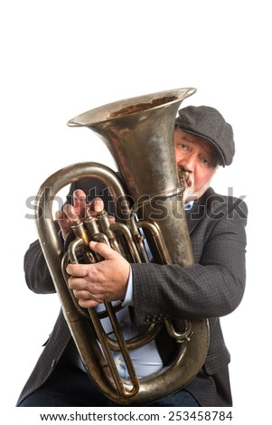 A man playing a vintage silver tuba, isolated on a white background - stock photo