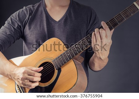 A Man Playing Acoustic Guitar in Black background . Photo for magazine ,or design work