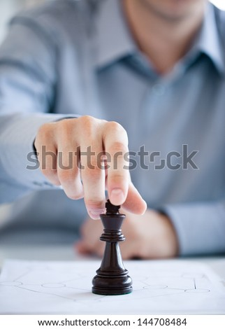 A man playing chess and thinking about a suitable strategy. - stock photo
